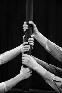 Zwei Händepaare fassen an den chinesischen Mast